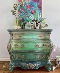 An ombre 3-drawered dresser that goes from light green on the top to dark green on the bottom.