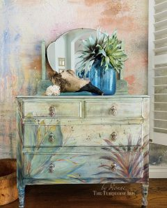 A sage green dresser with a green succulent and palm frond.