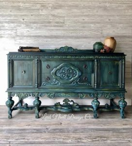 An opulent dark green end table by Leah Noell