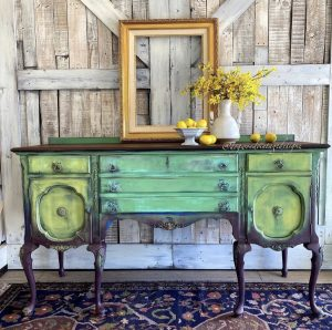 A very dramatic green sidebard with dark legs and various shades of green across the drawers