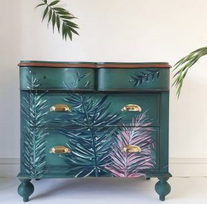 A dark green dresser with palm fronds painted in blues and purples.