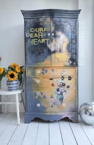 """painted wardrobe featuring a portrait of a woman and the words """"courage dear heart"""" in yellow"""