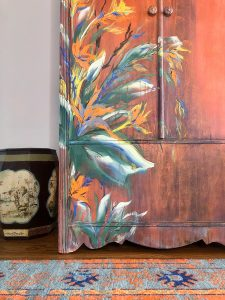 Close up of hand painted flowers on rust colored wardrobe